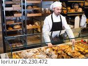 Купить «Smiling male pastry maker demonstrating croissant», фото № 26230472, снято 26 января 2017 г. (c) Яков Филимонов / Фотобанк Лори