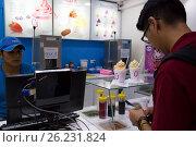 Buyer in the Fast food cafe Yogen Fruz with yogurt ice cream in a shopping mall of Santa Cruz, Bolivia (2016 год). Редакционное фото, фотограф Жукова Юлия / Фотобанк Лори