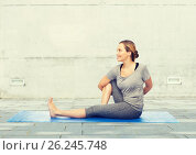 Купить «woman making yoga in twist pose on mat», фото № 26245748, снято 13 ноября 2015 г. (c) Syda Productions / Фотобанк Лори