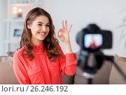 Купить «woman with camera recording video at home», фото № 26246192, снято 22 декабря 2016 г. (c) Syda Productions / Фотобанк Лори