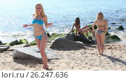 Купить «smiling girl in bikini standing on beach while her friends resting», видеоролик № 26247636, снято 22 июня 2016 г. (c) Яков Филимонов / Фотобанк Лори