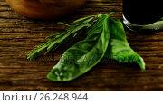 Купить «Herbs and bowl of red olives on wooden table», видеоролик № 26248944, снято 6 декабря 2019 г. (c) Wavebreak Media / Фотобанк Лори