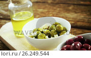 Купить «Red and green olives and olive oil on wooden board», видеоролик № 26249544, снято 6 декабря 2019 г. (c) Wavebreak Media / Фотобанк Лори