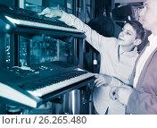 Купить «Father and teenage son examining keyboards in guitar shop», фото № 26265480, снято 29 марта 2017 г. (c) Яков Филимонов / Фотобанк Лори
