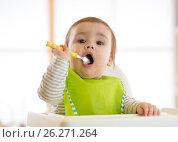 Купить «Happy baby boy spoon eats itself», фото № 26271264, снято 1 апреля 2017 г. (c) Оксана Кузьмина / Фотобанк Лори