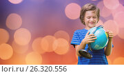 Купить «Smiling boy holding globe over bokeh», фото № 26320556, снято 16 июля 2019 г. (c) Wavebreak Media / Фотобанк Лори