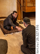 Купить «The iman of a mosque in Mission Viejo, CA, shakes hands with a parishioner after conducting a Muslim service. Note Oriental rug.», фото № 26327816, снято 19 февраля 2017 г. (c) age Fotostock / Фотобанк Лори