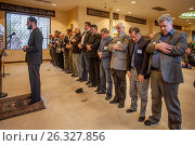Adult men prepare to pray during religious services at a mosque in Mission Viejo, CA. Note Iman at left conducting the service and man with arms hanging... (2017 год). Редакционное фото, фотограф Spencer Grant / age Fotostock / Фотобанк Лори
