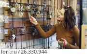 Купить «Young girl buyer looking of colored necklaces in the store», видеоролик № 26330944, снято 2 мая 2017 г. (c) Яков Филимонов / Фотобанк Лори
