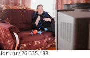 Купить «Old lady pensioner at home in glasses knitting in front of the TV», фото № 26335188, снято 19 февраля 2019 г. (c) Константин Шишкин / Фотобанк Лори