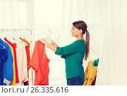 Купить «happy woman choosing clothes at home wardrobe», фото № 26335616, снято 19 февраля 2016 г. (c) Syda Productions / Фотобанк Лори