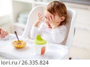 Купить «baby sitting in highchair and eating at home», фото № 26335824, снято 24 января 2017 г. (c) Syda Productions / Фотобанк Лори
