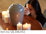 Купить «sad woman with funerary urn praying at church», фото № 26336012, снято 20 марта 2017 г. (c) Syda Productions / Фотобанк Лори