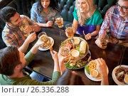 Купить «happy friends eating and drinking at bar or pub», фото № 26336288, снято 14 июля 2016 г. (c) Syda Productions / Фотобанк Лори
