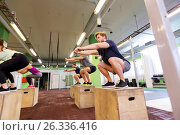 Купить «group of people doing box jumps exercise in gym», фото № 26336416, снято 19 февраля 2017 г. (c) Syda Productions / Фотобанк Лори