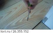 Купить «Male hand twist the screw into a wooden Board using a power screwdriver», видеоролик № 26355152, снято 21 мая 2017 г. (c) Роман Будников / Фотобанк Лори