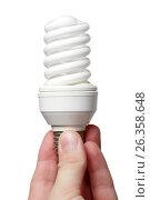 Купить «Энергосберегающая лампа в руке на белом фоне», фото № 26358648, снято 7 июля 2011 г. (c) Александр Гаценко / Фотобанк Лори