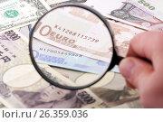 Купить «Лупа в руке фокусируется на банкнотах евро в окружении различных валют», фото № 26359036, снято 12 июля 2009 г. (c) Александр Гаценко / Фотобанк Лори