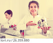 Купить «Female manicurist showing lacquer color schemes», фото № 26359880, снято 2 февраля 2017 г. (c) Яков Филимонов / Фотобанк Лори
