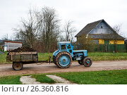 Tractor-trailer manure rides on a rural road. Стоковое фото, фотограф Никита Ковалёв / Фотобанк Лори