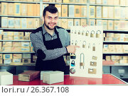 Купить «Adult male seller demonstrating assortment», фото № 26367108, снято 5 апреля 2017 г. (c) Яков Филимонов / Фотобанк Лори