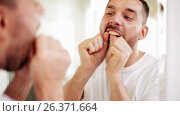 Купить «man with dental floss cleaning teeth at bathroom», видеоролик № 26371664, снято 20 января 2020 г. (c) Syda Productions / Фотобанк Лори