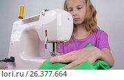 Купить «Девочка подросток обрабатывает края ткани на швейной машинке», видеоролик № 26377664, снято 27 мая 2017 г. (c) Круглов Олег / Фотобанк Лори