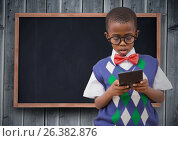 Купить «Boy in vest and bowtie with calculator against chalkboard and grey wood panel», фото № 26382876, снято 23 июля 2019 г. (c) Wavebreak Media / Фотобанк Лори