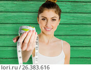 Купить «fitness woman apple and meter with green wood background», фото № 26383616, снято 26 апреля 2018 г. (c) Wavebreak Media / Фотобанк Лори