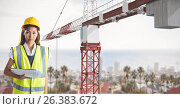 Купить «Female architect holding blue prints while standing by crane», фото № 26383672, снято 16 августа 2018 г. (c) Wavebreak Media / Фотобанк Лори