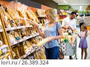 Купить «Woman choosing bread in bakery section», фото № 26389324, снято 15 августа 2018 г. (c) Яков Филимонов / Фотобанк Лори