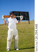 Cricket player holding bat while standing on field. Стоковое фото, агентство Wavebreak Media / Фотобанк Лори