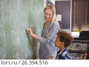 Купить «Teacher assisting schoolboy in writing alphabet on chalkboard», фото № 26394516, снято 11 марта 2017 г. (c) Wavebreak Media / Фотобанк Лори