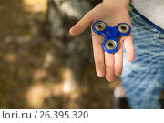Купить «Girl holding a fidget spinner in a park», фото № 26395320, снято 15 августа 2018 г. (c) Wavebreak Media / Фотобанк Лори