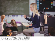 Купить «Schoolkids raising their hands while teacher teaching in classroom», фото № 26395608, снято 11 марта 2017 г. (c) Wavebreak Media / Фотобанк Лори