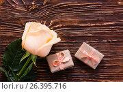 Свежая роза и пара упакованных подарков на деревянном фоне. Стоковое фото, фотограф Елена Руй / Фотобанк Лори