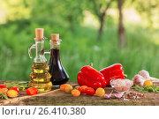 Купить «vegetables with oil on wooden table outdoor», фото № 26410380, снято 29 мая 2017 г. (c) Майя Крученкова / Фотобанк Лори