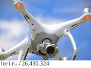 Купить «Drone DJI Phantom 4 in flight. Quadrocopter against the blue sky with white clouds. The flight of the copter in the sky.», фото № 26430324, снято 30 мая 2017 г. (c) Leonid Eremeychuk / Фотобанк Лори