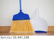 Купить «Dustpan and sweeping broom leaning against white wall», фото № 26441248, снято 21 октября 2016 г. (c) Wavebreak Media / Фотобанк Лори