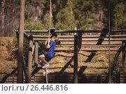 Купить «Determined girl climbing rope during obstacle course», фото № 26446816, снято 16 марта 2017 г. (c) Wavebreak Media / Фотобанк Лори