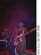 Купить «Singer playing guitar with male drummer in night club», фото № 26447048, снято 7 марта 2017 г. (c) Wavebreak Media / Фотобанк Лори