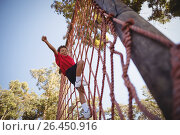 Купить «Happy boy cheering while climbing a net during obstacle course», фото № 26450916, снято 16 марта 2017 г. (c) Wavebreak Media / Фотобанк Лори