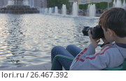 Купить «The boy is a teenager, sits in a beautiful spot by the fountain, and photographs water splashes. Beautiful landscape at sunset. A good place for rest and relaxation.», видеоролик № 26467392, снято 2 июня 2017 г. (c) Игорь Усачев / Фотобанк Лори
