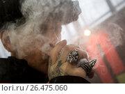 Купить «Посетитель выставки Vape Show курит электронные сигареты в городе Москве,  Россия», фото № 26475060, снято 22 апреля 2017 г. (c) Николай Винокуров / Фотобанк Лори