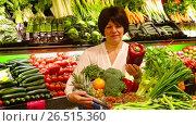 Mature woman choosing seasonal vegetables in farm food store. Стоковое видео, видеограф Яков Филимонов / Фотобанк Лори