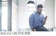 Купить «Young man typing a message on your phone», видеоролик № 26515908, снято 3 мая 2017 г. (c) Raev Denis / Фотобанк Лори