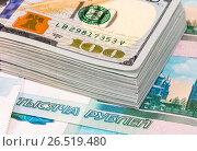 Купить «Stack of one hundred american dollar banknotes over roubles background», фото № 26519480, снято 9 января 2017 г. (c) FotograFF / Фотобанк Лори