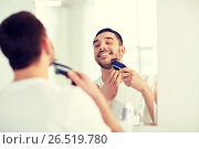 Купить «man shaving beard with trimmer at bathroom», фото № 26519780, снято 15 января 2016 г. (c) Syda Productions / Фотобанк Лори