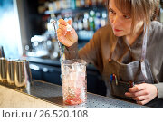 Купить «bartender adding essence to cocktail glass at bar», фото № 26520108, снято 7 февраля 2017 г. (c) Syda Productions / Фотобанк Лори