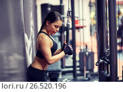 Купить «woman flexing arm muscles on cable machine in gym», фото № 26520196, снято 12 декабря 2015 г. (c) Syda Productions / Фотобанк Лори